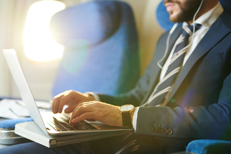 5 Crucial Cybersafety Tips for Business Travelers - Man wearing a suit and earbuds is visible from the waist up to his nose is on an airplane, working on a laptop