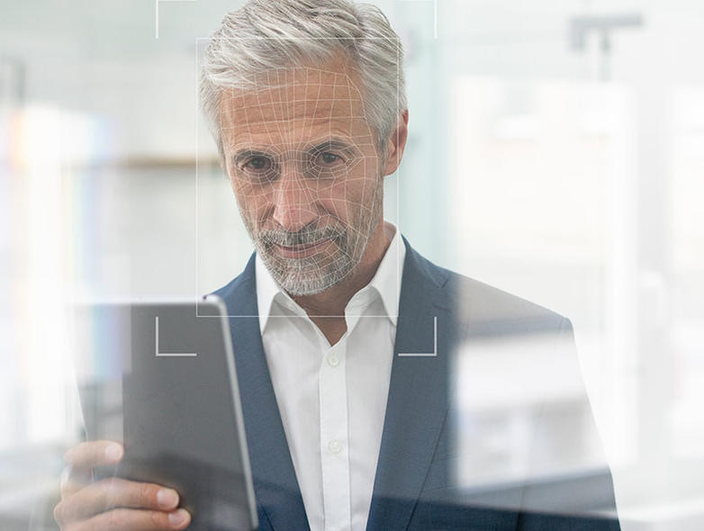 OneSpan - Man in suit, looking at his phone - scanning face